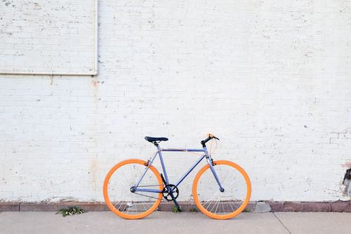 Orange and purple bike leaning against a white brick wall
