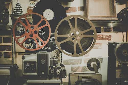 Two film reels against a patterned background