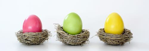 Pink, yellow, and green dyed eggs sit in their own individual small nests.