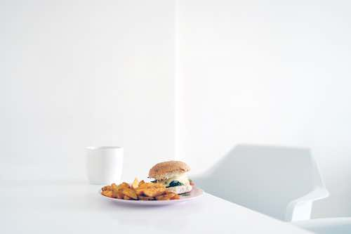 A burger on a white plate on a large white table