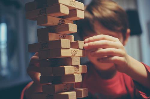 Unfocused image of young boy playing Jenga by stacking blocks