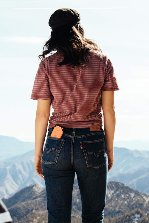 iPhone sticking half way out of back pocket of jeans, while woman looks at mountains in distance