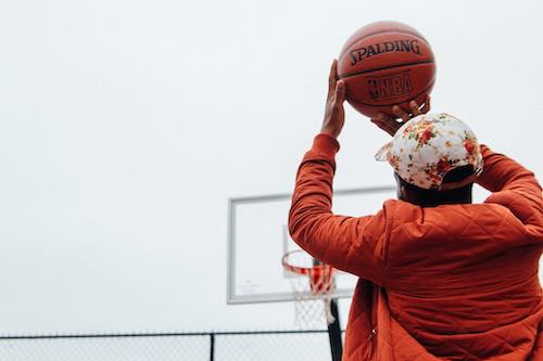 Person in orange jacket with flowered cap holding basketball above head about to shoot into hoop.